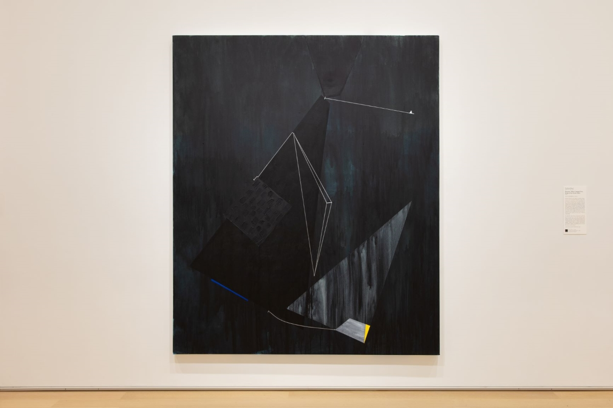 Large painting with geometric shapes in varied dark hues of black and blue colors and white, blue, and yellow shapes and lines hangs on a white wall.